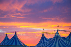 Circus tent in a dramatic sunset sky colorful. Orange blue with lights Stock Photos
