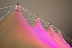 Circus tent at night. Lit up by red lights. Dark sky in the background Royalty Free Stock Photo