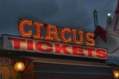 Circus tickets neon sign. Large bright circus tickets sign with part of funfair tent visible on one side Stock Photography