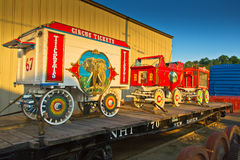Circus Wagons on Flatbed Railcar. Three vintage traveling circus wagons on a railroad flatbed, parked on a siding. Their bright colors flare in the low spring Stock Photo