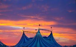 Circustent in een dramatische kleurrijke zonsonderganghemel stock foto
