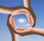 Cirkel av händer mot den blåa skyen Royaltyfria Bilder