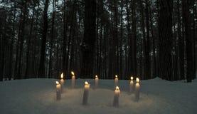 Cirkel av stearinljus i mörk vinterskog Arkivfoto