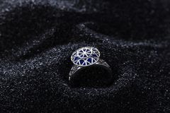 Cirkel för diamantformsilver med blåa gemstones på svart sand royaltyfri foto