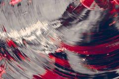 Cirkelglasspaanders van grijze kleur met gebroken plonsen van heldere rode en roze kleur, Stock Afbeelding