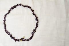 Cirkeln göras av kvinnliga härliga pärlor, halsband av bruna mörka stenar, bärnsten med en bakgrund av beige tyg Royaltyfri Foto