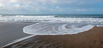 Cirkelseafoam van Vreedzame oceaangolven die over het strand wassen en in een getijdemoeras in Ventura California de V.S. stromen stock foto