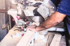 Cirkelzaag voor scherpe raad in de handen van het professionele timmerman, reparatie en bouwhulpmiddel stock afbeelding