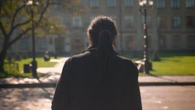 Cirkla runt om sikt av afrikansk amerikanstudenten med dreadlocks som går till universitetet och döljer från solsken stock video