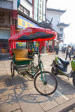 CirkuleringsRickshaw i en upptagen gata, Zhujiajiao, Kina Royaltyfri Bild
