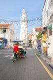 Cirkuleringsrickshawen rider ner gatan, Penang, Malaysia royaltyfri bild