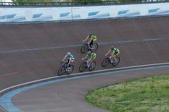 Cirkuleringsspår Springa på cirkuleringsspåret Flicka-cyklist på cycen Arkivfoton