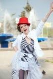 Cirkuskonstnärkvinna i en röd hatt utomhus Arkivfoton