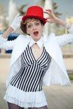 Cirkuskonstnärkvinna i röd hatt med ett förvånat uttryck på honom Royaltyfria Foton
