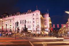 Cirque populaire de Picadilly de touriste avec le cric des syndicats de drapeaux dans la nuit Image stock