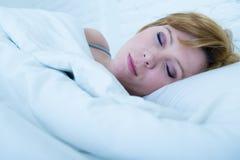 Ciérrese encima de cara de la mujer atractiva joven con el pelo rojo que duerme pacífico mintiendo en cama en casa Fotos de archivo