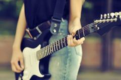 Ciérrese encima de la foto del jugador de la hembra de la guitarra Fotos de archivo libres de regalías