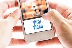 Ciérrese encima de la mano dos que sostiene el teléfono elegante con palabra video viral y Fotografía de archivo libre de regalías