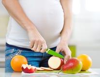 Ciérrese encima de las frutas de los cortes de la mujer embarazada Imágenes de archivo libres de regalías
