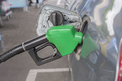 Ciérrese encima de surtidor de gasolina. y coche en la gasolinera Foto de archivo libre de regalías