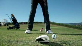 Ciérrese encima de tiro en un campo de golf cuando un golfista golpea la pelota de golf blanca con un golf metrajes