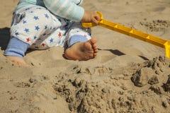 Ciérrese encima del bebé que juega con los juguetes de la arena en la playa Foto de archivo