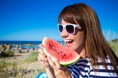 Ciérrese encima del retrato de la mujer hermosa que come la sandía en la playa Fotos de archivo