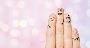 Ciérrese para arriba de cuatro fingeres con las caras sonrientes Fotos de archivo libres de regalías