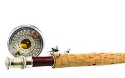 Ciérrese para arriba de la barra y del carrete de pesca con mosca en el fondo blanco Imagen de archivo