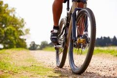 Ciérrese para arriba de la bici de montaña del montar a caballo del hombre en la trayectoria del campo Foto de archivo libre de regalías
