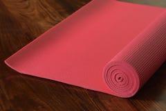 Ciérrese para arriba de la estera rosada de la yoga Fotografía de archivo