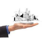 Ciérrese para arriba de la mano del hombre con bosquejo de la ciudad del smartphone Imagen de archivo libre de regalías