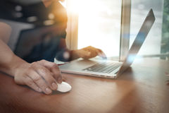 Ciérrese para arriba de la mano del hombre de negocios que trabaja en el ordenador portátil en la madera Foto de archivo libre de regalías