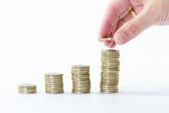 Ciérrese para arriba de la mano femenina que apila monedas de un euro en columnas cada vez mayores Fotografía de archivo