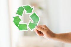 Ciérrese para arriba de la mano que lleva a cabo verde reciclan símbolo Foto de archivo libre de regalías
