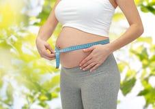 Ciérrese para arriba de la mujer embarazada que mide su panza Fotografía de archivo libre de regalías