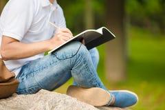 Ciérrese para arriba de las manos del muchacho que estudian para el examen de la universidad Imagen de archivo libre de regalías