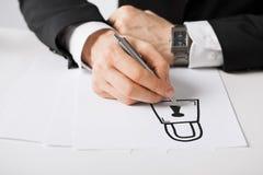 Ciérrese para arriba de las manos masculinas con la cerradura del dibujo de la pluma Imagen de archivo libre de regalías