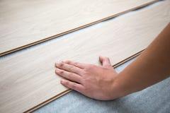 Ciérrese para arriba de las manos que instalan el nuevo piso de madera laminado Imagen de archivo libre de regalías