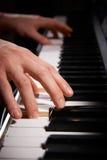 Ciérrese para arriba de las manos que juegan el teclado de piano eléctrico Fotos de archivo libres de regalías