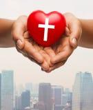 Ciérrese para arriba de las manos que llevan a cabo el corazón con símbolo cruzado Foto de archivo libre de regalías