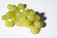 Ciérrese para arriba de las uvas sabrosas del gimoteo en el fondo blanco Imagen de archivo libre de regalías