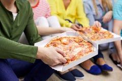 Ciérrese para arriba de los amigos felices que comen la pizza en casa Imagenes de archivo