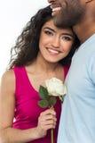 Ciérrese para arriba de los pares interraciales que sostienen la rosa del blanco Imagen de archivo