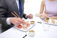 Ciérrese para arriba de los pares que comen el sushi en el restaurante Imágenes de archivo libres de regalías