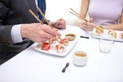 Ciérrese para arriba de los pares que comen el sushi en el restaurante Foto de archivo libre de regalías