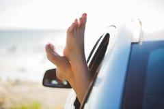Ciérrese para arriba de los pies de la mujer que muestran de la ventanilla del coche Imágenes de archivo libres de regalías