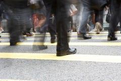 Ciérrese para arriba de los pies de los viajeros que cruzan la calle muy transitada Foto de archivo libre de regalías