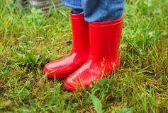 Ciérrese para arriba de los pies del niño que caminan en botas rojas en hierba verde Foto de archivo