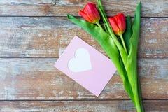 Ciérrese para arriba de tulipanes y de tarjeta de felicitación con el corazón Foto de archivo libre de regalías